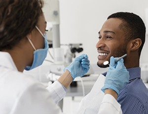 young man smiling at dentist while getting dental bonding in Carrollton