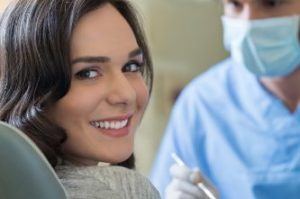 A smiling female patient in the dental chair