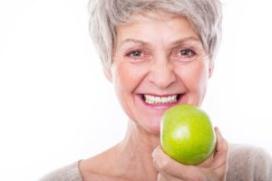 Older woman with dental implants in Carrollton holding an apple.