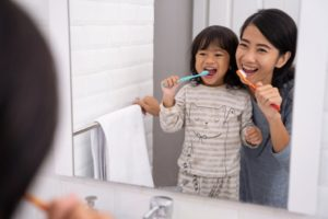 Mom and daughter brushing their teeth