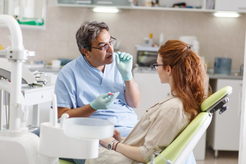 a male dentist in Plano talking with a female patient during an appointment