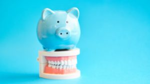 Blue piggy bank atop model teeth from Carrollton dentist