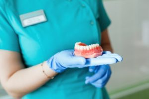 Closeup of dentist holding dentures in Carrollton